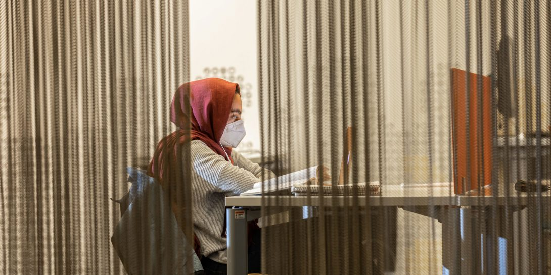 Patron studying in a hijab and mask.