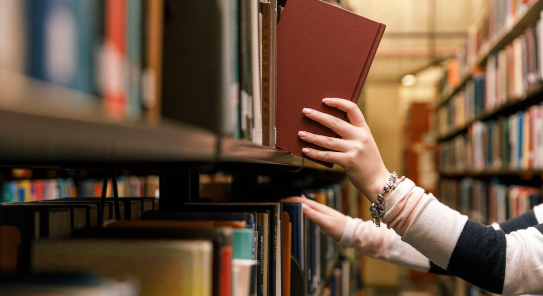 Librarian hands pulling books from a shelf.