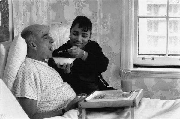 Hospice worker feeding an elderly patient in bed.