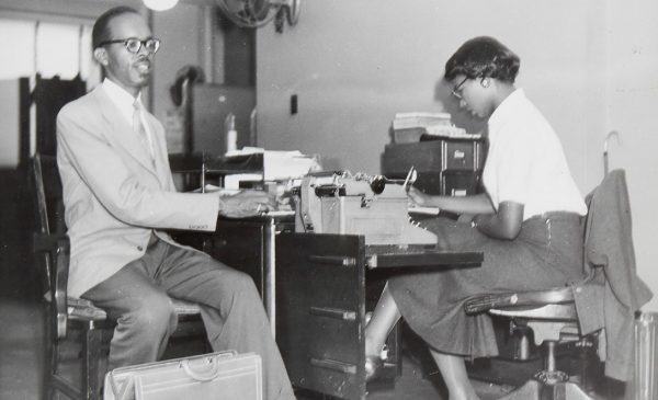 Scheltes collection archival greyscale photograph of a Black blind man with a briefcase, sitting beside a desk. A Black woman is sitting at the desk, looking down and writing.